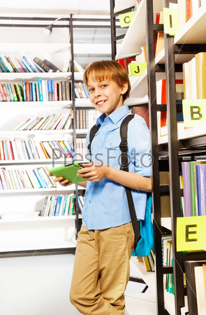 Smiling schoolboy stands and holds books