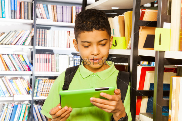 Boy playing with tablet in library