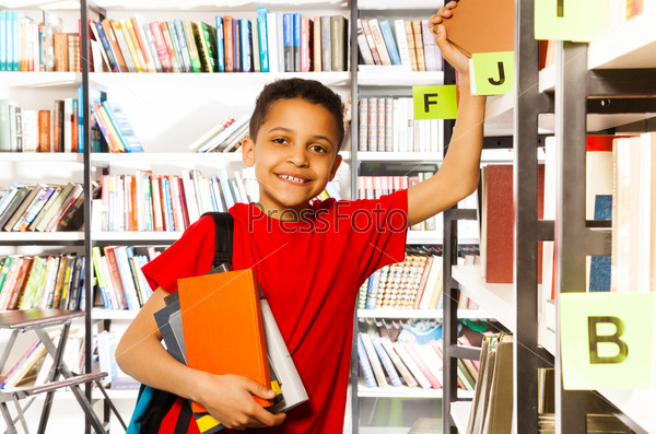 Cute boy with hand on bookshelf holds many books