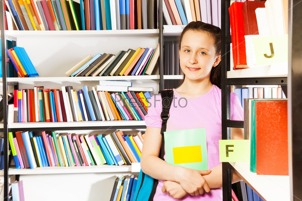 Smiling girl stands near bookshelf with textbook