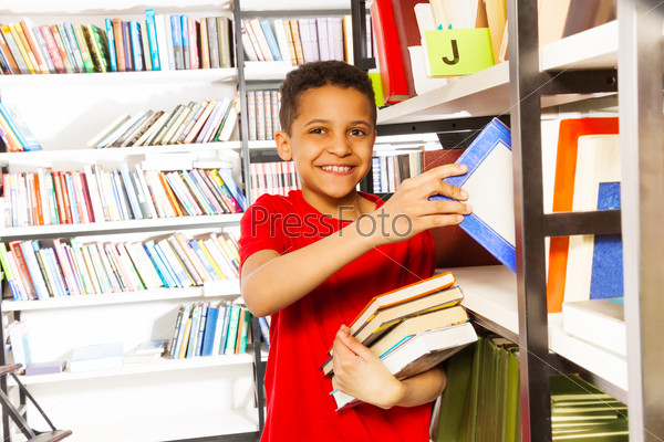 Happy boy with hand on bookshelf holds many books