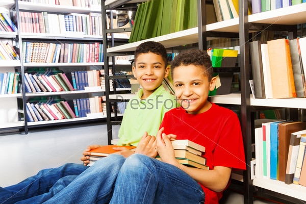 Two happy boys sitting on the floor in library