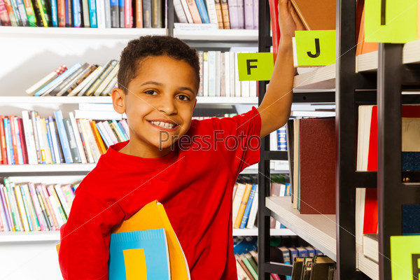 Smiling boy puts hand on bookshelf and holds book