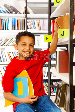 Smiling boy with hand on bookshelf holds books