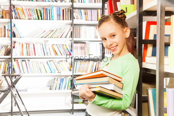Schoolgirl smiles and holds books in library