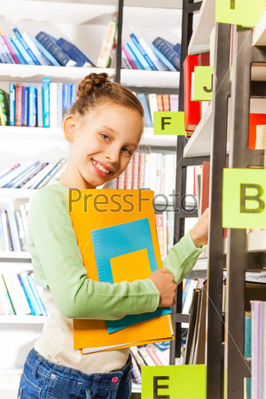 Cute girl searching books on the bookshelf