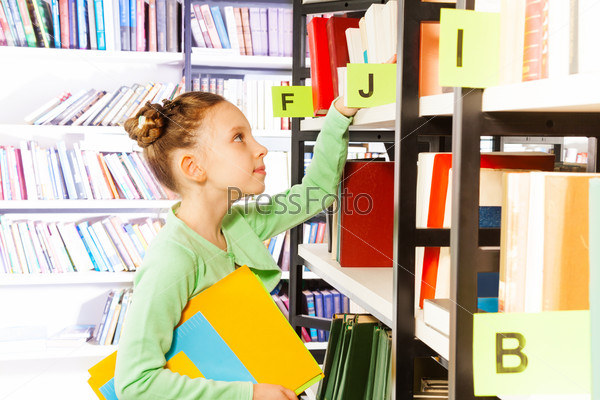 Girl looking and searching books in library