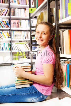 Smiling girl sitting on floor near bookshelf