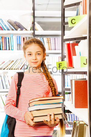 Girl with braid holds books near bookshelf