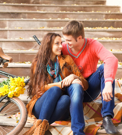 Happy young couple with bicycle walking in autumn