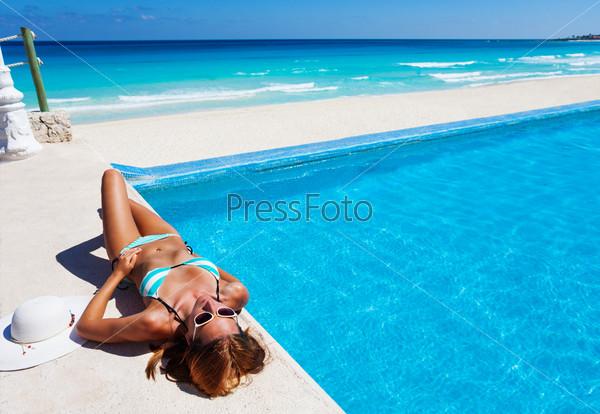 Girl resting near swimming pool in summer