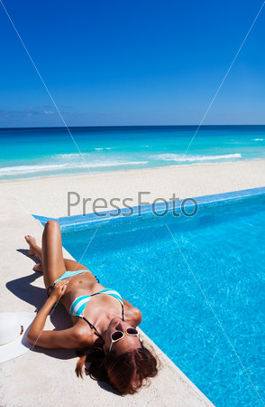 Girl with sunglasses rests near swimming pool