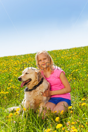 Smiling girl cuddling dog sitting on the grass