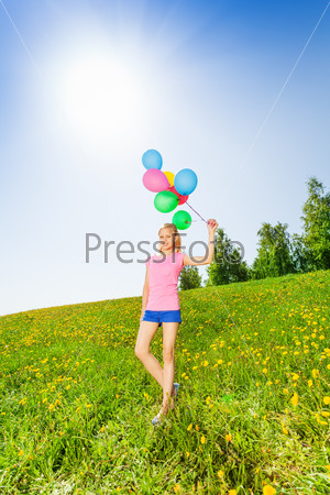 Standing girl with balloons in summer
