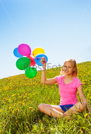 Sitting positive girl with balloons in summer