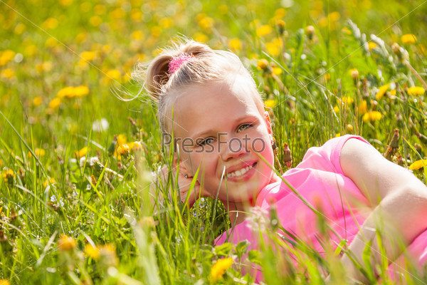 Smiling blond girl in yellow flowers portrait