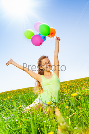 Smiling girl holding colorful balloons in summer
