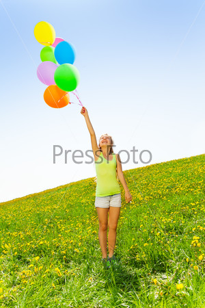 Happy girl holding colorful balloons in summer