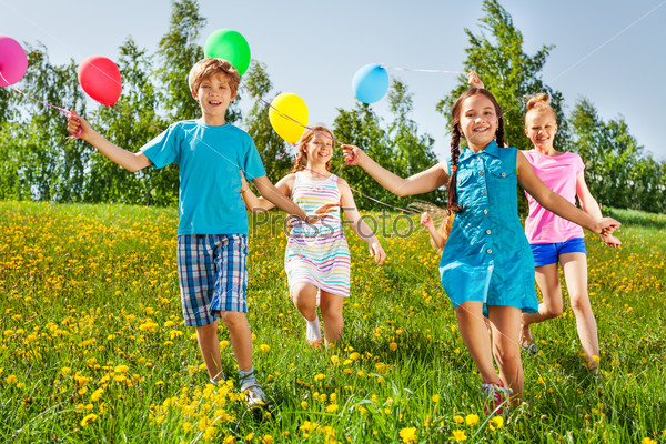 Running happy kids with balloons in green field