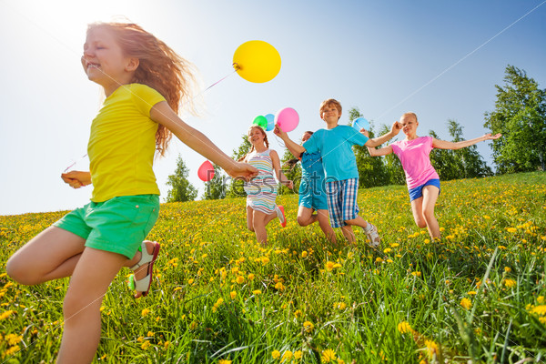 Excited kids with balloons run in field
