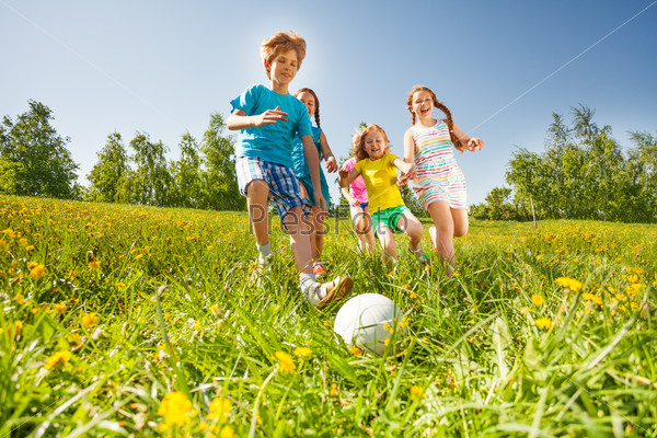 Happy kids playing football in green field