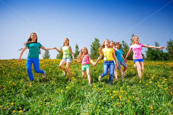 Happy children run and hold hands in green meadow