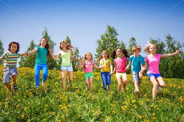 Playful children run, hold hands in green field