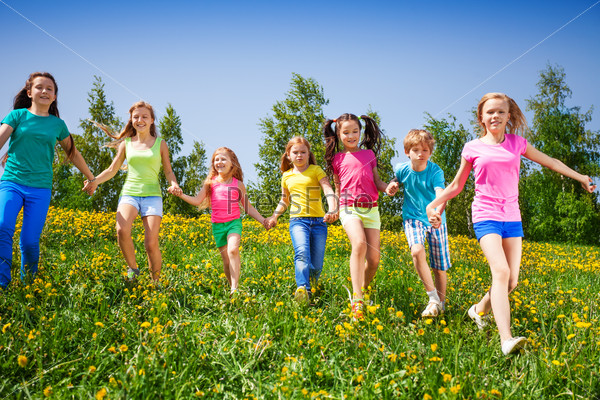 Happy children run and hold hands in green field