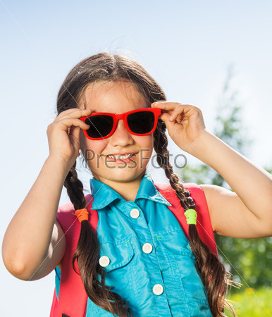 Smiling girl wearing sunglasses with two braids