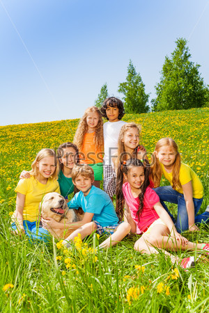 Happy children with dog together in meadow