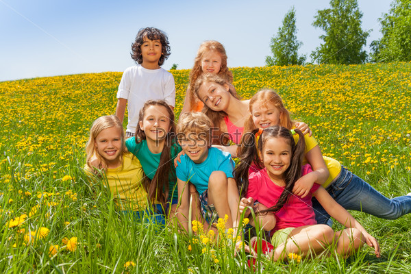 Smiling kids sitting together on the green  grass