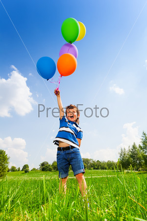 Excited boy with colorful balloons in green park