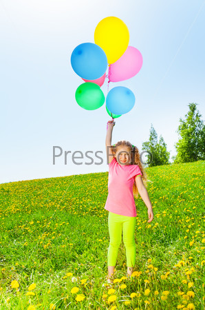 Happy girl with flying balloons stands on grass
