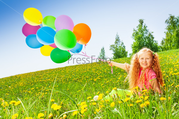Cheerful girl with flying balloons sits on grass
