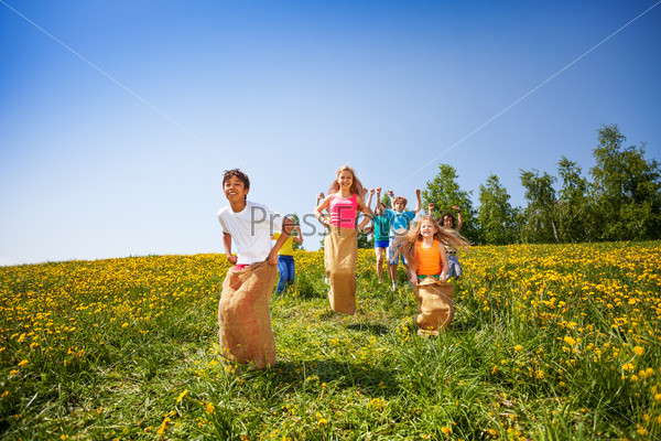 Playing children jump in sacks together