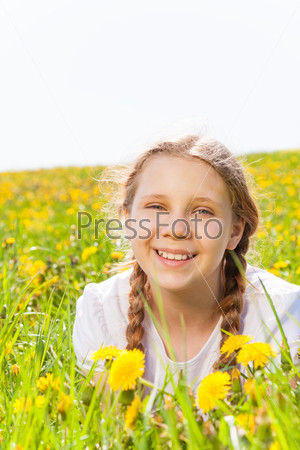 Smiling girl laying in dandelions meadow