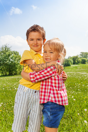 Boy and girl hugging in green field