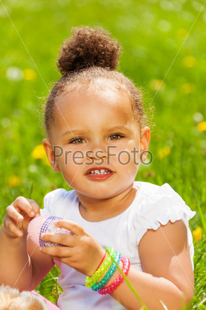 Portrait of cute curly girl with Eastern egg
