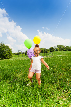 Little girl holding three flying balloons in park