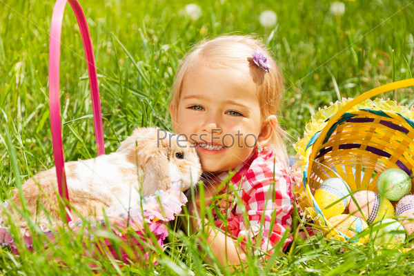 Cute small girl cuddling rabbit in field
