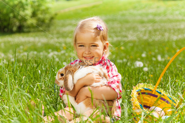 Small girl hugging rabbit in field