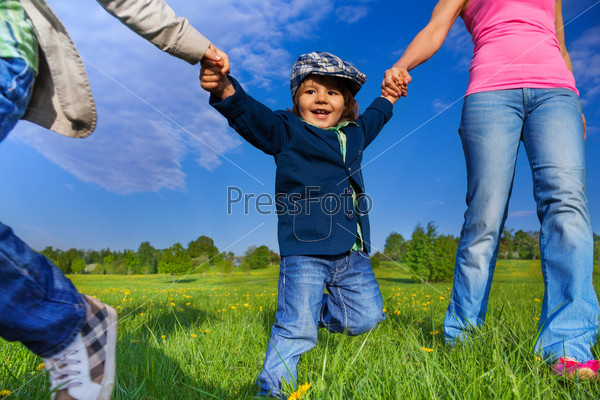Happy kid holding parents hands in park
