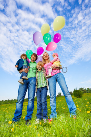 Parents and kids stand with balloons in park