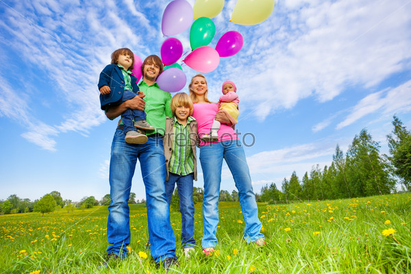 Happy family stands with balloons in park