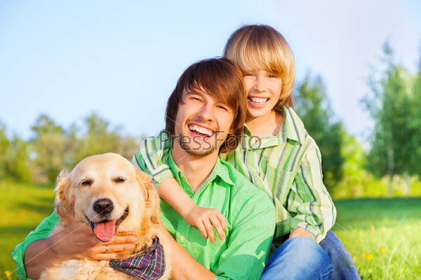 Smiling boy, father and dog sit in park on grass