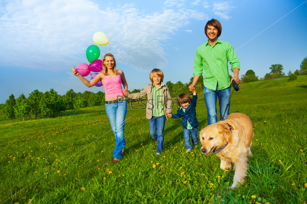 Happy family walks with balloons and dog in park