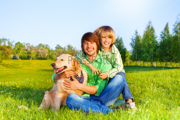 Smiling father, kid  and dog sit in park on grass