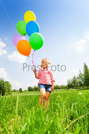 Small blond girl with many balloons in park