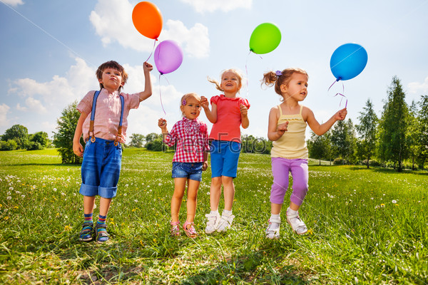 Small kids with four balloons in green meadow