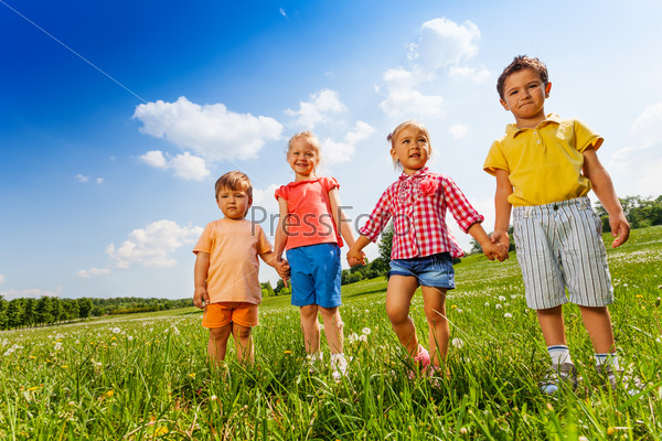 Four children holding hands and standing together